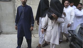 FILE - In this Aug. 10, 2018 file photo, a security official escorts family members of suicide bomber Hafeez Nawaz, with their faces covered for interrogation in Karachi, Pakistan. Nawaz killed149 people and wounding 300 others. At age 20, Hafeez Nawaz left his religious school in Karachi to join the Islamic State group in Afghanistan. Three years later he was back in Pakistan to carry out a deadly mission. (AP Photo/Fareed Khan)