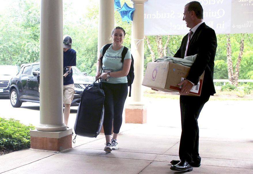 Cathleen Dacey, 23, a Quinnipiac University law student, gets help from Masonicare CEO J.P. Venoit, right, as she moves into Masonicare at Ashlar Village, a retirement community in Wallingford, Conn. Dacey will live at the center this school year as part of an intergenerational learning program. (AP Photo/Pat Eaton-Robb)