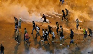 People run as riot police charges to clear the square during protests outside the government headquarters, in Bucharest, Romania, Friday, Aug. 10, 2018. Romanians who live abroad are staging an anti-government protest calling on the left-wing government to resign and an early election. (AP Photo/Vadim Ghirda) ** FILE **