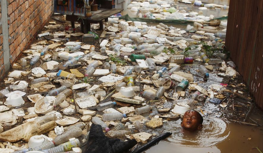 In this Saturday, Aug. 11, 2018, photo, a boy swims near floating trash during flood season in the floating village on the Mekong river bank on the outskirts of Phnom Penh, Cambodia. (AP Photo/Heng Sinith, File)