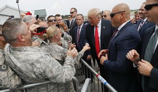 President Donald Trump greets members of the military on the tarmac upon his arrival on Air Force One at Francis S. Gabreski Airport in Westhampton, N.Y., Friday, Aug. 17, 2018. Trump traveled to New York for a campaign fundraiser with supporters and will then travel to Bedminster, N.J, to spend the weekend at his private golf resort. (AP Photo/Pablo Martinez Monsivais)