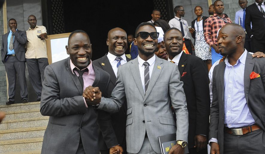 """In this photo taken Tuesday, July 11, 2017, Ugandan pop star Kyagulanyi Ssentamu, better known as Bobi Wine, center, leaves shortly after being sworn in as a member of parliament in Kampala, Uganda. The 36-year-old """"ghetto child"""" is a new member of parliament who urges his countrymen to stand up against what he calls a failing government but was charged Thursday, Aug. 16, 2018 in a military court over his alleged role in clashes in the northwestern town of Arua where both he and President Yoweri Museveni were campaigning. (AP Photo/Ronald Kabuubi)"""