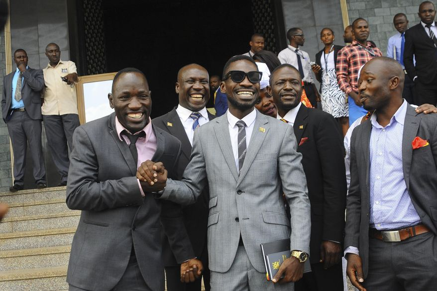 "In this photo taken Tuesday, July 11, 2017, Ugandan pop star Kyagulanyi Ssentamu, better known as Bobi Wine, center, leaves shortly after being sworn in as a member of parliament in Kampala, Uganda. The 36-year-old ""ghetto child"" is a new member of parliament who urges his countrymen to stand up against what he calls a failing government but was charged Thursday, Aug. 16, 2018 in a military court over his alleged role in clashes in the northwestern town of Arua where both he and President Yoweri Museveni were campaigning. (AP Photo/Ronald Kabuubi)"
