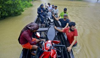 People salvage motorcycles in a country boat in a flooded area at Kainakary in Alappuzha district, Kerala state, India, Friday, Aug. 17, 2018. Rescuers used helicopters and boats on Friday to evacuate thousands of people stranded on their rooftops following unprecedented flooding in the southern Indian state of Kerala that killed more than 320 people in the past nine days, officials said. (AP Photo/Tibin Augustine)