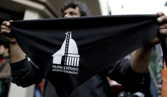 "A seller offers handkerchiefs reading in Spanish ""Church and state- Separate issues"" in Buenos Aires, Argentina Saturday, Aug. 18, 2018. People formed lines on Saturday as part of a nationwide movement in the homeland of Pope Francis to file forms with their name and signature to renounce their religious affiliation, after a bill to legalize elective abortions in the first 14 months of pregnancy was finally rejected by Senators in recent weeks. (AP Photo/Natacha Pisarenko)"