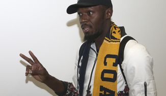 Jamaica's Usain Bolt waves as he arrives in Sydney, Saturday, Aug. 18, 2018. Olympic gold medalist sprinter, Bolt is hoping to impress the coaching staff enough to earn a contract with the Central Coast Mariners for the 2018-19 season in Australia's top-flight soccer competition.(AP Photo/Rick Rycroft)