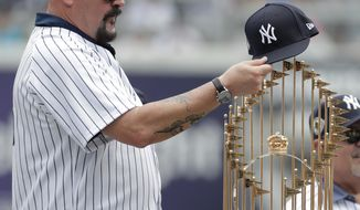 Former New York Yankees pitcher David Wells puts his hat on the 1998 World Series trophy during a ceremony honoring the team prior to a baseball game between the New York Yankees and the Toronto Blue Jays, Saturday, Aug. 18, 2018, in New York. (AP Photo/Julio Cortez)