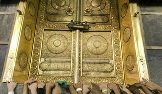 Muslim pilgrims touch the golden door of the Kaaba, the cubic building at the Grand Mosque, as they pray ahead of the annual Hajj pilgrimage in the Muslim holy city of Mecca, Saudi Arabia, Friday, Aug. 17, 2018. The annual Islamic pilgrimage draws millions of visitors each year, making it the largest yearly gathering of people in the world. (AP Photo/Dar Yasin)