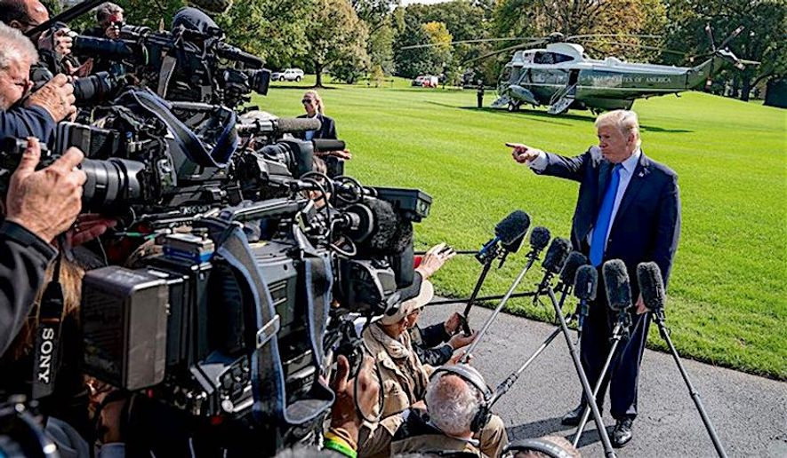 A familiar scene: President Trump stands and fields a constant barrage of questions from news reporters earlier this summer. (Associated Press)