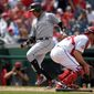 The Miami Marlins' Starlin Castro scores past Washington Nationals catcher Matt Wieters on a sacrifice fly by JT Riddle in a five-run fifth inning on Sunday. The Nationals fell 12-1 to the last-place Marlins for their second 11-run loss of the season. The Nationals have now lost four of their last seven games to the Marlins. (Associated Press)
