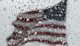 An American flag is seen through rain drops on a window as rain falls in Baltimore, Sunday, April 22, 2012. (AP Photo/Patrick Semansky)