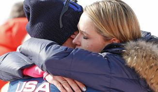Morgan Miller hugs her husband, United States' Bode Miller after he took part in the flower ceremony for the men's super-G for his joint bronze medal at the Sochi 2014 Winter Olympics, Sunday, Feb. 16, 2014, in Krasnaya Polyana, Russia. (AP Photo/Gero Breloer)