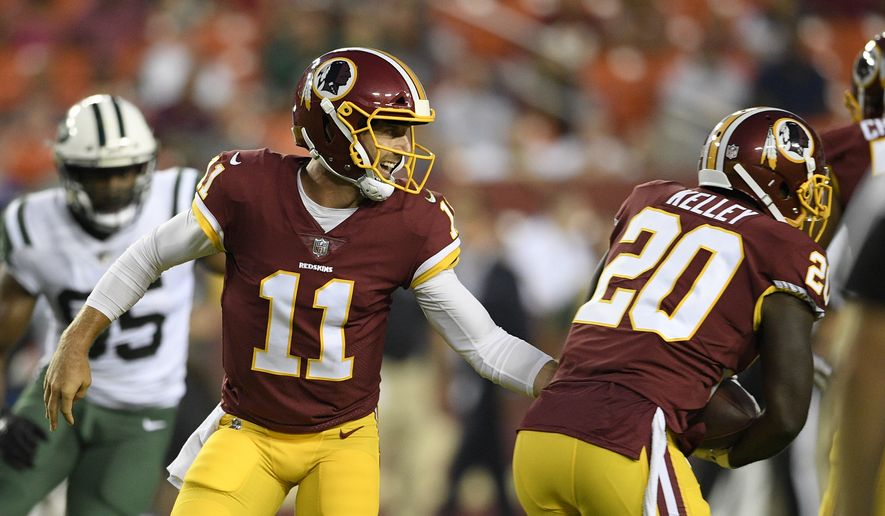 Washington Redskins quarterback Alex Smith (11) hands off to running back Rob Kelley (20) during the first half of a preseason NFL football game against the New York Jets, Thursday, Aug. 16, 2018, in Landover, Md. (AP Photo/Nick Wass)