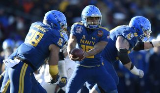 FILE- In this Dec. 28, 2017, file photo Navy quarterback Malcolm Perry hands off to Anthony Gargiulo against Virginia in the first half of the Military Bowl NCAA college football game in Annapolis, Md. Navy is handing the keys to its triple-option offense to Perry, who was the starting slotback for eight games last season before coach Ken Niumatalolo switched him to quarterback to spark a struggling offense. (AP Photo/Gail Burton) ** FILE **