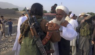 In this June 16, 2018, file photo, Taliban fighters gather with residents to celebrate a three-day cease fire marking the Islamic holiday of Eid al-Fitr, in Nangarhar province, east of Kabul, Afghanistan. On Sunday, Aug. 19, 2018, Afghan President Ashraf Ghani announced a conditional cease-fire with Taliban insurgents for the duration of the Eid al-Adha holiday. Ghani made the announcement Sunday during celebrations of the 99th anniversary of Afghanistan's independence. (AP Photo/Rahmat Gul, File)