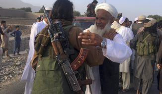 FILE - In this June 16, 2018 file photo, Taliban fighters gather with residents to celebrate a three-day cease fire marking the Islamic holiday of Eid al-Fitr, in Nangarhar province, east of Kabul, Afghanistan. On Sunday, Aug. 19, 2018, Afghan President Ashraf Ghani announced a conditional cease-fire with Taliban insurgents for the duration of the Eid al-Adha holiday. Ghani made the announcement Sunday during celebrations of the 99th anniversary of Afghanistan's independence. (AP Photo/Rahmat Gul, File)