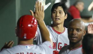 Los Angeles Angels' Shohei Ohtani (17) high-fives Albert Pujols (5) after Ohtani's pinch-hit three-run home run against the Texas Rangers during the seventh inning of a baseball game Saturday, Aug. 18, 2018, in Arlington, Texas. (AP Photo/Richard W. Rodriguez)