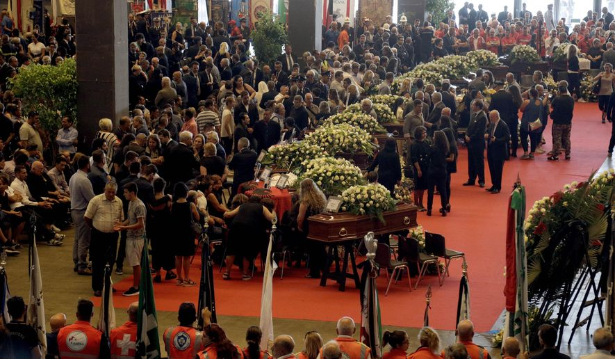 People gather for a funeral service for some of the victims of a collapsed highway bridge, in Genoa's exhibition center Fiera di Genova, Italy, Saturday, Aug. 18, 2018. Saturday has been declared a national day of mourning in Italy and includes a state funeral at the industrial port city's fair grounds for those who plunged to their deaths as the 45-meter (150-foot) tall Morandi Bridge gave way Tuesday. (AP Photo/Gregorio Borgia)