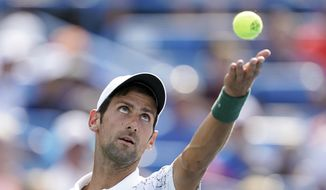 Novak Djokovic, of Serbia, serves to Roger Federer, of Switzerland, during the finals at the Western & Southern Open tennis tournament, Sunday, Aug. 19, 2018, in Mason, Ohio. (AP Photo/John Minchillo)