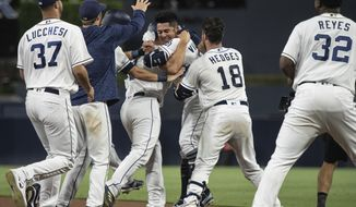 San Diego Padres celebrate after Christian Villanueva, center right, hit a walk-off single against the Arizona Diamondbacks during a baseball game in San Diego, Saturday, Aug. 18, 2018. The Padres won 7-6. (AP Photo/Kyusung Gong)