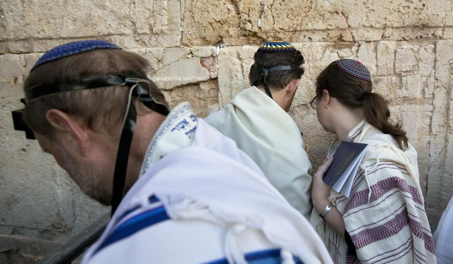 In this Thursday, Feb. 25, 2016, file photo, American and Israeli Reform rabbis pray at the Western Wall, the holiest site where Jews can pray in Jerusalem's old city. Israel's recent detentions of Jewish-American critics entering the country is shining a spotlight on a growing gulf between the country's hard-line government and the predominantly liberal Jewish community in the U.S. (AP Photo/Sebastian Scheiner, File)