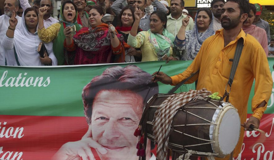 Supporters of Pakistan Tahreek-e-Insaf party headed by Imran Khan, shout slogans on traditional drum beat to celebrate the success of their leader, in Lahore, Pakistan, Saturday, Aug. 18, 2018. Pakistan's cricket star-turned-politician Imran Khan was sworn in as prime minister on Saturday despite protests by opposition parties, which accuse the security services of intervening on his behalf in last month's elections. (AP Photo/K.M. Chaudary)