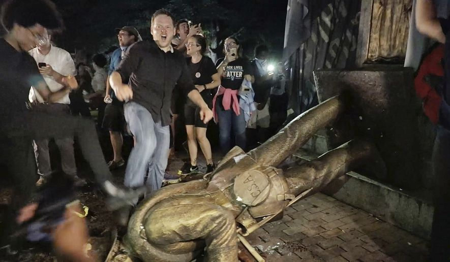 "Protesters celebrate after the Confederate statue known as ""Silent Sam"" was toppled on the campus of the University of North Carolina in Chapel Hill, N.C., Monday, Aug. 20, 2018. (Julia Wall/The News & Observer via AP)"