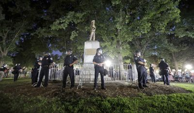 "FILE - In this Tuesday, Aug. 22, 2017 file photo, police surround the ""Silent Sam"" Confederate monument during a protest to remove the statue at the University of North Carolina in Chapel Hill, N.C. In North Carolina, officials are trying to determine whether this and other Confederate memorials have become public safety hazards _ a determination that opponents believe could fulfill an exception to a 2015 law preventing their permanent removal. (AP Photo/Gerry Broome, File)"