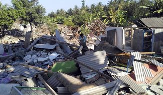 A man inspects destroyed homes following an earthquake on Lombok island, Indonesia, Monday, Aug. 20, 2018. Multiple strong earthquakes killed a number of people on the Indonesian islands of Lombok and Sumbawa as the region was trying to recover from a temblor earlier this month that killed hundreds of people. (AP Photo/Fauzy Chaniago)