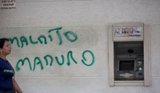 "A wall is spray painted with a message that reads in Spanish: ""Damn Maduro"" next to an ATM machine in Caracas, Venezuela, Monday, Aug. 20, 2018. Banks remained closed Monday as they prepare to release the ""sovereign bolivar,"" the new currency printed with five fewer zeroes in a bid to tame soaring inflation. (AP Photo/Ariana Cubillos)"