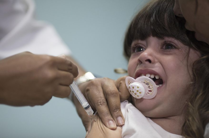 In this file photo dated Monday, Aug. 6, 2018, a child receives a measles vaccination in Rio de Janeiro, Brazil.  The World Health Organization (WTO) said Monday Aug. 20, 2018, the number of measles cases in Europe jumped sharply during the first six months of 2018 with at least 37 people dead from the disease, and called for increased immunization rates to prevent an endemic.  (AP Photo/Leo Correa, FILE)