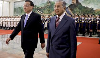 Malaysia's Prime Minister Mahathir Mohamad, right, walks with Chinese Premier Li Keqiang after reviewing an honor guard during a welcome ceremony at the Great Hall of the People in Beijing, Monday, Aug. 20, 2018. (AP Photo/Andy Wong)