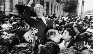 FILE - In this Sept. 27, 1951 file photo, Iranian Prime Minister Mohammad Mossadegh rides on the shoulders of cheering crowds in Tehran's Majlis Square, outside the parliament building, after reiterating his oil nationalization views to his supporters. In 2018, as Iran deals with President Donald Trump's decision to pull America from the nuclear deal with world powers, more are invoking the 1953 CIA-backed coup that toppled Mossadegh as proof the U.S. cannot be trusted. (AP Photo, File)