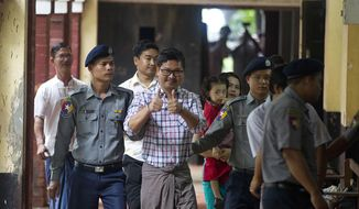 """Reuters journalist Wa Lone gives a """"thumbs up"""" as he is escorted by police upon arrival to his trial Monday, Aug. 20, 2018, in Yangon, Myanmar. The two reporters, Wa Lone and Kyaw Soe Oo are accused of illegally possessing official information. (AP Photo/Thein Zaw)"""