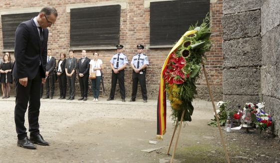 German Foreign Minister Heiko Maas bows in front of the Death Wall, after laying a wreath in the former German Nazi Death Camp Auschwitz Birkenau in Oswiecim, Poland, Monday, Aug. 20, 2018. (AP Photo/Jarek Praszkiewicz)