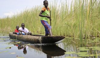In this photo taken Wednesday, Aug. 15, 2018, people travel by canoe between small islands off the mainland from the opposition-held town of Nyal in Unity state, in South Sudan. The government claims a shattering five-year civil war is finally over, but skepticism soars and the latest attempt at peace already shows cracks. (AP Photo/Sam Mednick)