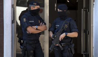 Catalan police officers stand guard at the entrance of a building during a raid, following an attack in Cornella de Llobregat near Barcelona, Spain, Monday, August 20, 2018. Police in Barcelona say they have shot a man who attacked officers with a knife at a police station in the Spanish city, saying in a tweet Monday the attack occurred just before 6 a.m. in the Cornella district of the city. (AP Photo/Emilio Morenatti)