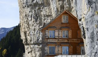 FILE - In this Oct. 14, 2014 file photo people take a break outside the Gasthaus Aescher near Ebenalp, Switzerland. The Gasthaus Aescher, built into a cliff above a valley in northeastern Switzerland, has been run by the same family since 1987.  Authorities in Appenzell-Innerrhoden canton said Monday, Aug. 20, 2018 that the current tenants, Nicole and Bernhard Knechtle-Fritsche, are giving up the lease at the end of the 2018 season. (Steffen Schmidt/Keystone via AP)