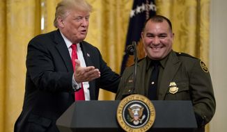 President Donald Trump welcomes Customs and Border Patrol agent Adrian Anzaldua, right, on stage to speak during an event to salute U.S. Immigration and Customs Enforcement (ICE) officers and U.S. Customs and Border Protection (CBP) agents in the East Room of the White House in Washington, Monday, Aug. 20, 2018. (AP Photo/Andrew Harnik)