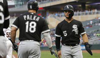 Chicago White Sox's Yolmer Sanchez, right, is greeted by Daniel Palka after scoring on a two-run double by Jose Abreu off Minnesota Twins pitcher Stephen Gonsalves in the second inning of a baseball game Monday, Aug. 20, 2018, in Minneapolis. (AP Photo/Jim Mone)