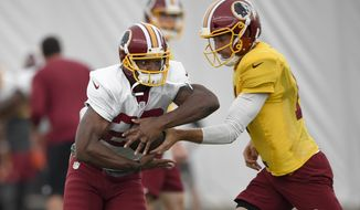 Washington Redskins running back Adrian Peterson, left, takes the handoff from quarterback Alex Smith, right, during an NFL football team practice, Tuesday, Aug. 21, 2018, in Ashburn, Va. (AP Photo/Nick Wass)