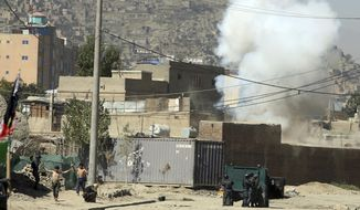 Smoke rises from a house where suspected attackers were hiding while policemen arrests two suspects, left, in Kabul, Afghanistan, Tuesday, Aug. 21, 2018. The Taliban fired rockets toward the presidential palace in Kabul Tuesday as President Ashraf Ghani was giving his holiday message for the Muslim celebrations of Eid al-Adha, said police official Jan Agha. (AP Photo/Rahmat Gul)