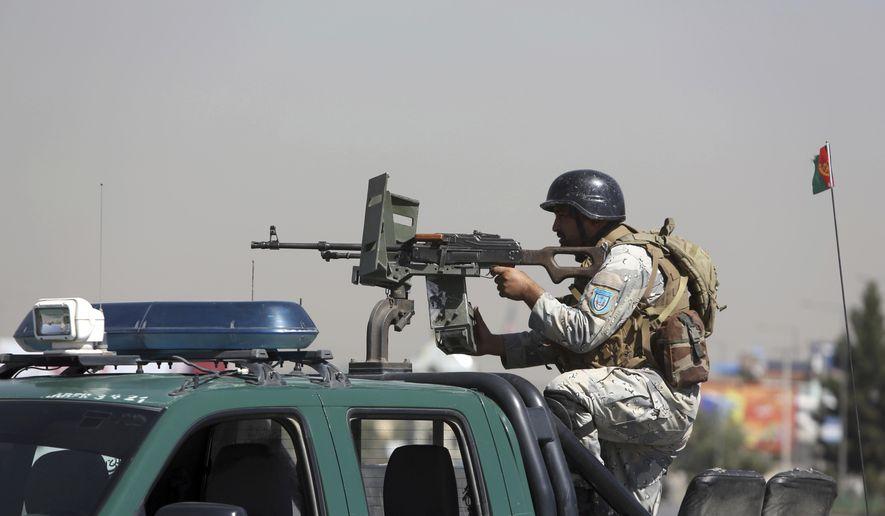 An Afghan security officer mans with gun near a house where attackers are hiding, in Kabul, Afghanistan, Tuesday, Aug. 21, 2018. Afghan police say the Taliban fired rockets toward the presidential palace in Kabul as President Ashraf Ghani was giving his holiday message for the Muslim celebrations of Eid al-Adha. (AP Photo/Rahmat Gul)