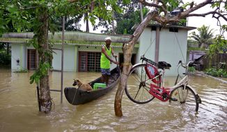 A bicycle is hung from a tree branch to avoid being washed away in flood waters as a man rows with his dog in a country boat at Kuttanad in Alappuzha in the southern state of Kerala, India, Monday, Aug. 20, 2018. Kerala has been battered by torrential downpours since Aug. 8, with floods and landslides killing at least 250 people. About 800,000 people now living in some 4,000 relief camps. (AP Photo/Tibin Augustine)