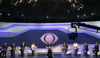 FILE - In this Aug. 9, 2018 file photo, debate mediator Ricardo Boechat, center, stands with Brazil's presidential candidates before the start of a debate in Sao Paulo, Brazil, ahead of October elections. From left are Alvaro Dias of Podemos Party, Cabo Daciolo of Patriota Party, Geraldo Alckmin of the Social Democratic Party, Marina Silva of the Sustainability Network Party, Jair Bolsonaro of the National Social Liberal Party, Guilherme Boulos of the Socialism and Liberty Party, Henrique Meirelles of the Democratic Movement Party, and Ciro Gomes of the Democratic Labor Party. General elections are set for October. (AP Photo/Andre Penner, File)