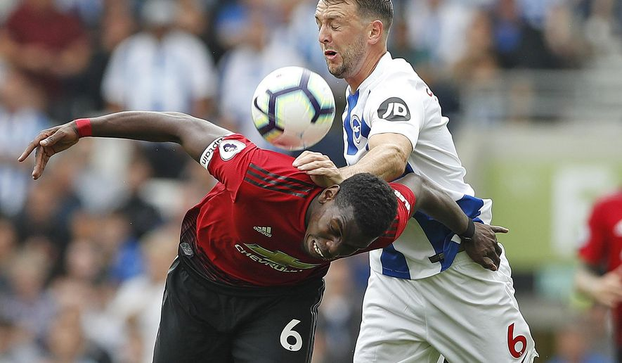 Manchester United's Paul Pogba, left, and Brighton's Dale Stephens battle for the ball during the English Premier League soccer match between Brighton and Hove Albion and Manchester United at the Amex stadium in Brighton, England, Sunday, Aug.19, 2018. (AP Photo/Alastair Grant)