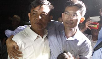 Two former Radio Free Asia reporters Uon Chhin, left, and Yeang Socheamet, right, hold together after they walk outside the main prison of Prey Sar at the outskirt of Phnom Penh, Cambodia, Tuesday, Aug. 21, 2018. Two Cambodian journalists who had worked for U.S.-funded Radio Free Asia and are charged with espionage have been released on bail, a day after a pardon freed four land rights activists from prison. (AP Photo/Heng Sinith)