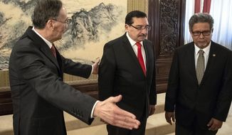 Chinese Vice President Wang Qishan, left, shows the way to Medardo Gonzalez, center, a Salvadoran politician, Secretary General of the ruling party of El Salvador, and El Salvador Foreign Minister Carlos Castaneda during their meeting at the Zhongnanhai Leadership Compound in Beijing Tuesday, Aug. 21, 2018. Taiwan broke off diplomatic ties with El Salvador on Tuesday as the Central American country defected to rival Beijing in the latest blow to the self-ruled island China has been trying to isolate on the global stage. (Roman Pilipey/Pool Photo via AP)