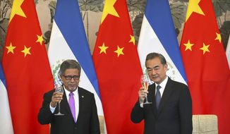 El Salvador's Foreign Minister Carlos Castaneda and China's Foreign Minister Wang Yi celebrate a toast at a signing ceremony to mark the establishment of diplomatic relations between El Salvador and China at the Diaoyutai State Guesthouse in Beijing, China, Tuesday, Aug. 21, 2018. (AP Photo/Mark Schiefelbein)