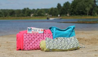 This Aug. 19, 2018 photo shows three tote-able towels on the beach in Hopkinton, N.H, Beach towels can pull double duty or at least be easier to carry if you add straps to turn them into tote bags. (AP Photo/Holly Ramer)